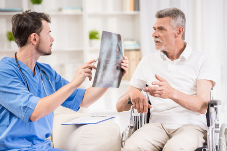 medicalcare: Male doctor showing diagnosis of xray image to older patient sitting at wheelchair.