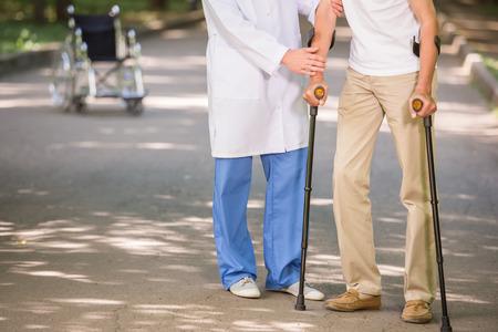 ayudando: Primer plano de médico ayudar a su paciente a caminar con muletas.