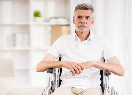 Senior man sitting in wheelchair at home.