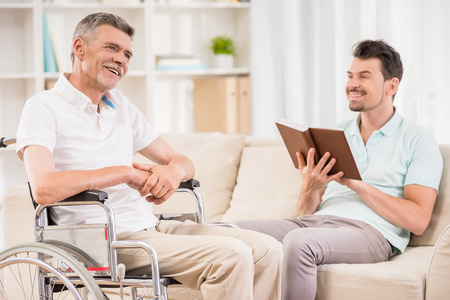 Adult man sitting at home and reading book to his eldery father in wheelchair. Stock Photo