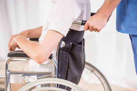 retirement  age: Closeup of male nurse taking care about senior patient in wheelchair at clinic. Stock Photo