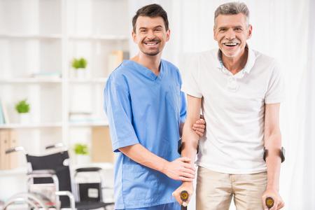 Kind male nurse helping senior patient on ctutches.