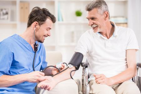 Mannelijke arts meten van de bloeddruk van oudere patiënt zittend op rolstoel. Stockfoto