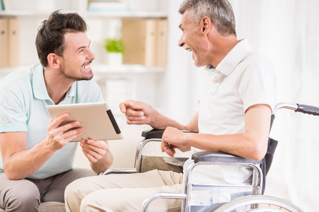 Smiling handsome man showing digital tablet to his eldery father in wheelchair.