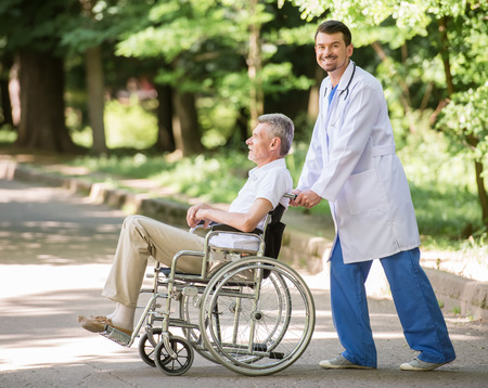 garden staff: Male nurse walking with senior patient in wheelchair in garden near hospital. Side view. Stock Photo