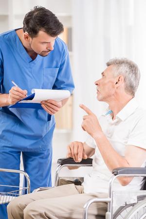 enfermera con paciente: Enfermero cuidando sobre el paciente mayor en silla de ruedas. Foto de archivo