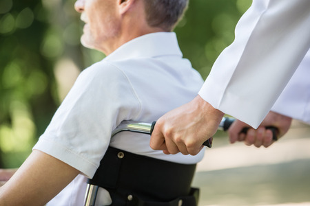 Male nurse walking with senior patient in wheelchair in garden near hospital. Closeup.