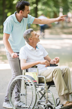frailty: Adult son walking with disabled father in wheelchair at park. Side view. Stock Photo