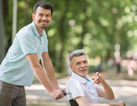 an elderly person: Hijo adulto que recorre con el padre discapacitado en silla de ruedas en el parque.
