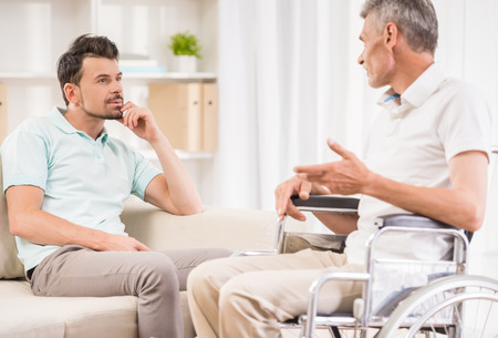 mobility nursing: Adult man sitting at home and talking to his eldery father in wheelchair.