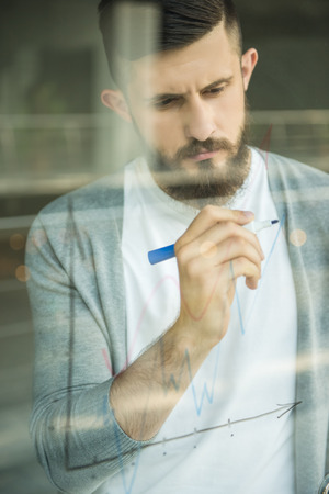 drawing a plan: Creative man drawing business strategy at office window. Stock Photo