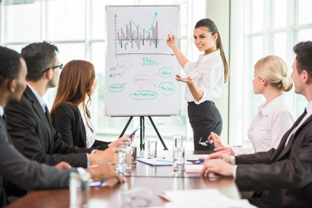 Business woman pointing at a growing chart during a meeting,