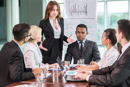 Young business people in suits sitting at meeting room and listening speaker. Stock Photo