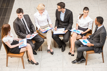 round collar: Group of  businesspeople in suits sitting in circle and discussing marketing results.