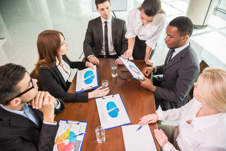 financial concept: Image of confident colleagues communicating with their boss at meeting.