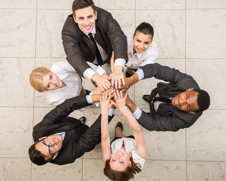 round collar: Group of  businesspeople in suits standing in circle and putting hands together.
