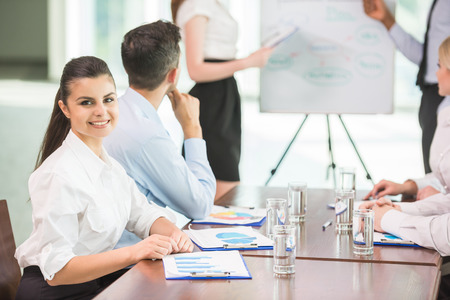 commenting: Confident business people commenting marketing results to colleagues at meeting. Stock Photo