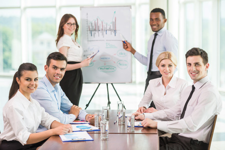 Confident business people commenting marketing results to colleagues at meeting. Stock Photo