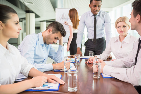 employee: Business team at a meeting in a modern office environment.