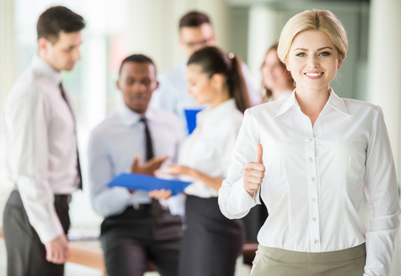 successful woman: Successful woman at the office leading a business team. Stock Photo