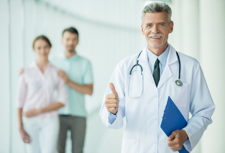 gynaecologist: Cheerful doctor standing at clinic and smiling at camera with patients on background.