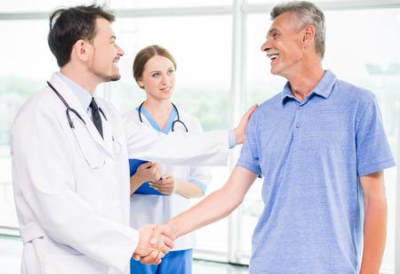 행복 남성 환자와 그의 자신감이 의사의 손을 흔들면서.