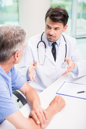 elderly patient: Male doctor talking with patient seriously at clinic.