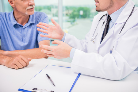 urologist: Male doctor talking with patient seriously at clinic. Close-up.