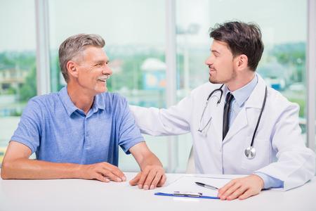 Knappe mannelijke arts bemoedigend zijn volwassen patiënt. Stockfoto - 41697262