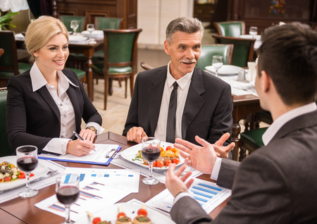 almuerzo: Grupo de hombres de negocios exitosos en discusiones contrato durante el almuerzo de negocios.