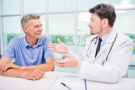 Male doctor talking with patient seriously at clinic.