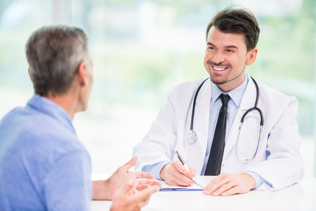 doctor clipboard: Smiling handsome doctor talking with patient at his office. Stock Photo