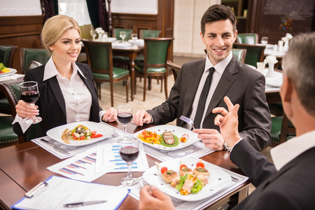 formal dinner party: Group of successful business people celebrating a great deal agreement. Stock Photo
