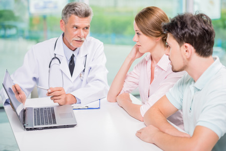 gynaecologist: Experienced male doctor explaining to his patients results of analysis with laptop.