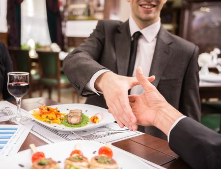 to lunch: Dos socios de negocios elegantes que sacuden las manos mientras almorzaba negocio. Gran acuerdo de reparto.