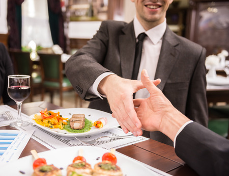 busy restaurant: Two elegant business partners shaking hands while having business lunch. Great deal agreement.