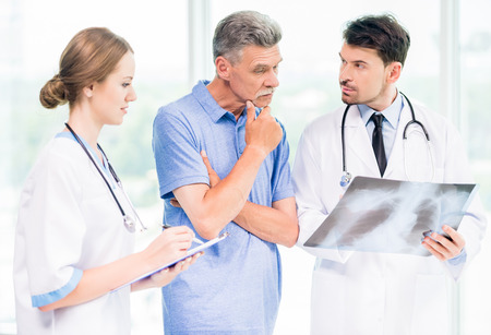 Doctors and patient discussing X-ray results in diagnostic center. Stock Photo