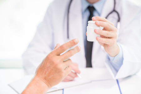 pill: Close-up of male doctor giving jar of pills to patient.