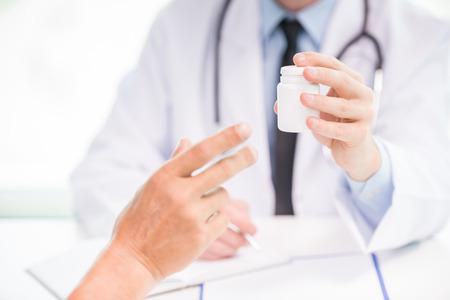consulta médica: Primer plano de sexo masculino médico que den frasco de pastillas para el paciente. Foto de archivo