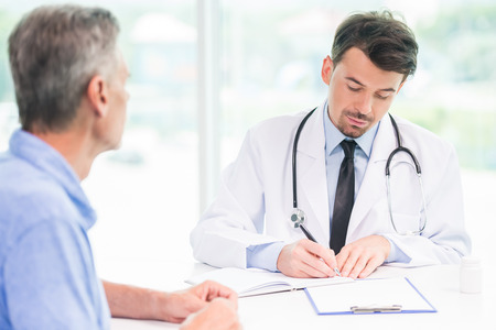 patient notes: Male doctor talking with patient and writing down recipe for medicine.