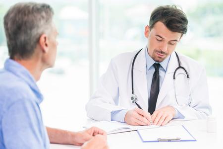 paciente: Masculino médico hablando con el paciente y escribir receta para el medicamento. Foto de archivo