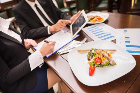 healthy lunch: Close-up of business people working on marketing strategy during business lunch. Stock Photo