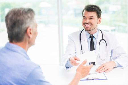 Smiling handsome doctor talking with patient at his office. Standard-Bild