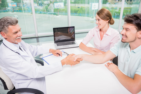 gynaecologist: Mature male doctor greeting his new patients at clinic. Stock Photo