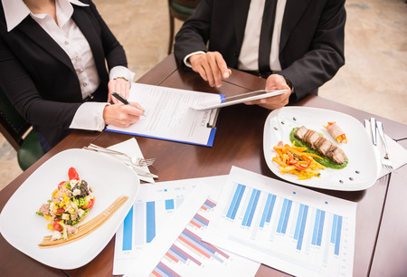 lunch meal: Close-up of business people working on marketing strategy during business lunch. Stock Photo
