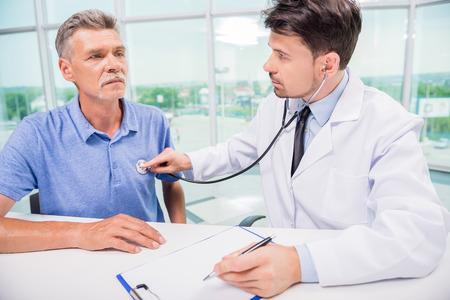 visit: Male medical doctor examining his mature patient with stethoscope.