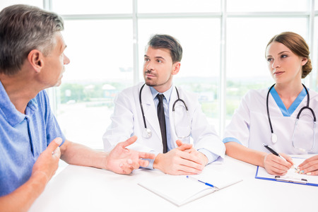 hospital patient: Doctors explaining diagnosis to mature male patient in hospital. Stock Photo