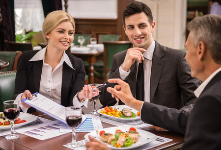 deals: Confident business partners in suits discussing contract during business lunch.