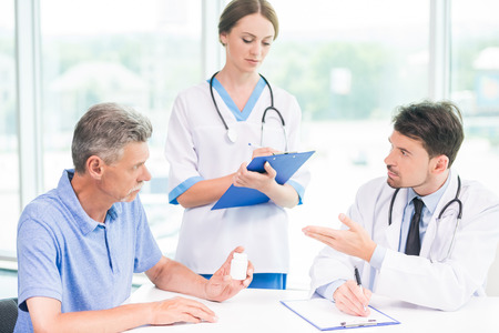 hospital patient: Two young doctors consulting patient in hospital. Stock Photo