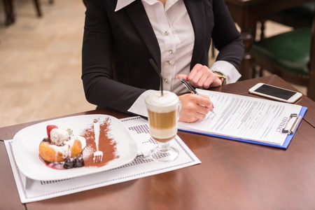 business table: Confident woman in suit reading contract during business lunch.